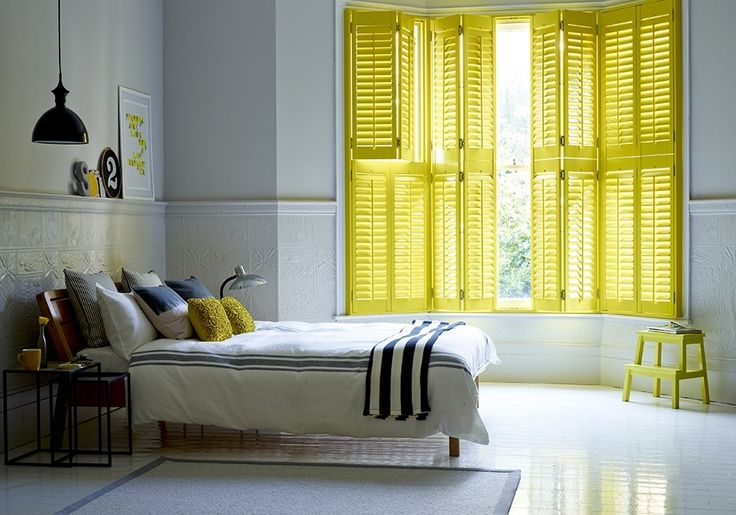 This bedroom uses tier on tier shutters to give full light control for the room. The shutters consist of 64mm slats with central pushrods and are finished in a custom yellow shade. The vibrant yellow used draws bright light into the room and gives a real summery feel, perfect for those days it may not be quite so summery outside! Please note 10% surcharge applies to custom colours.