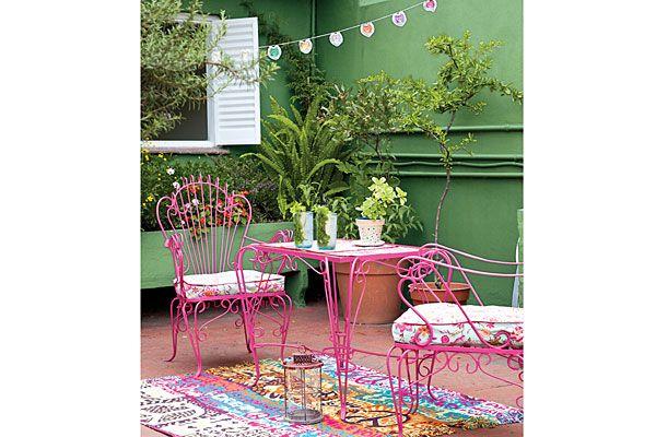 Un juego de hierro (mesa-sillas) rosa le da un toque vintage y colorido al espacio