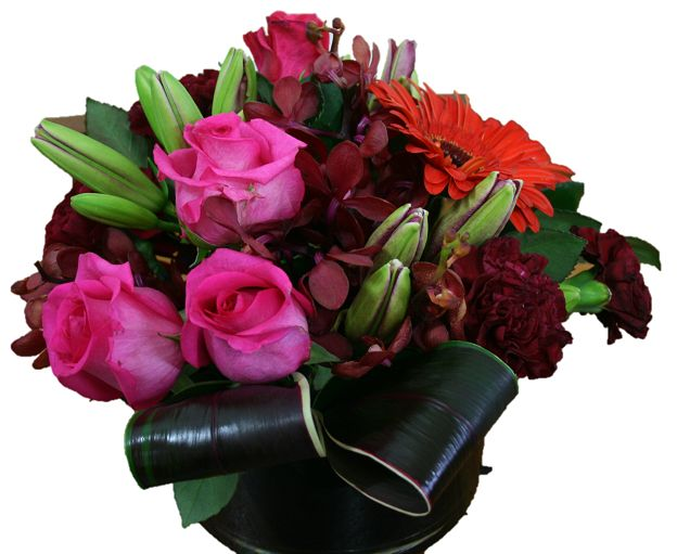 A glass vase filled with red and pink roses and flowers and foliage -  https://bloominboxes.com.au/melody