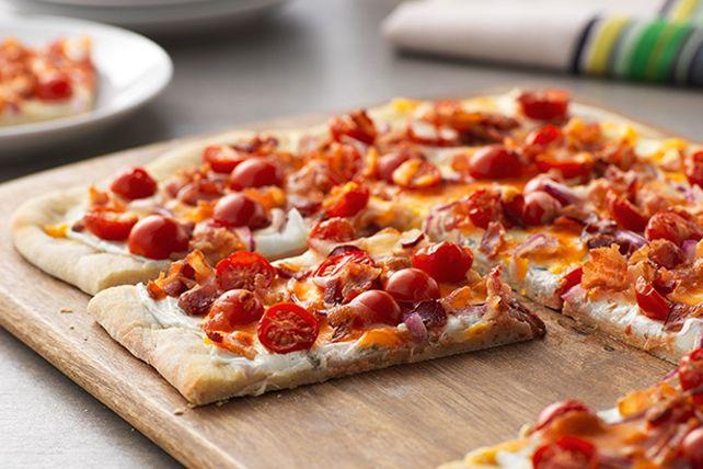 Le fromage à la crème piquant avec jalapeno constitue la base de cette délicieuse recette. Garni de tomates, d'oignon, de bacon et de fromage râpé, ce pain plat fera assurément partie de vos recettes favorites.