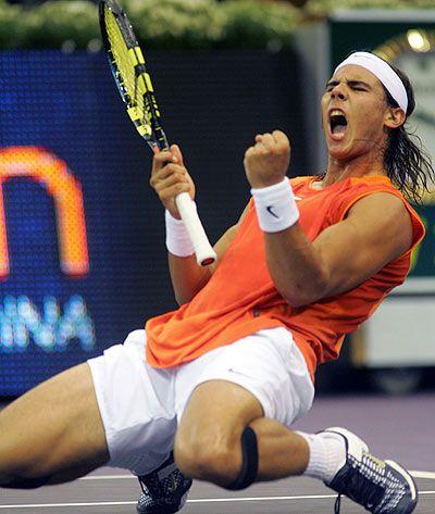 Rafael Nadal es de  España, él lleva unos pantalones cortos blancas y una camiseta anaranjada, unos zapatos de tenis son grises y amarillos, él lleva unos calcetines blancos.