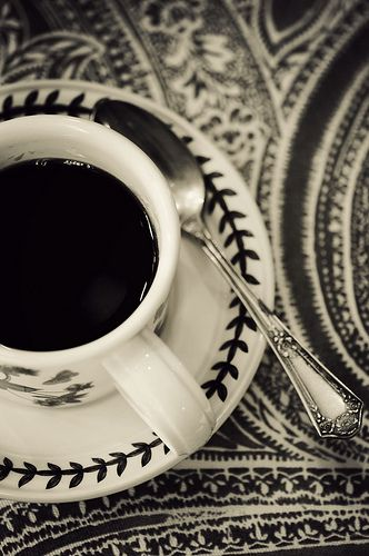 coffee...in a cup...with a spoon...on a saucer...on pretty table cover