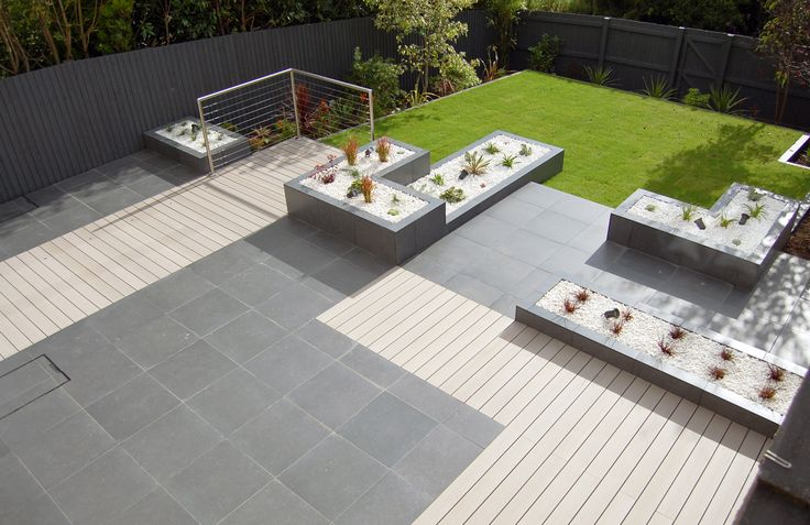 Porcelain paving and clad walls with composite decking for Modern garden decking designs