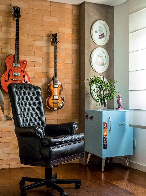 O fundo da sala tem parede de tijolinhos, da Cia das Telhas, onde o morador gosta de expor seus instrumentos musicais. A poltrona herdada da família ganhou rodízios (Foto: Edu Castello/Editora Globo)