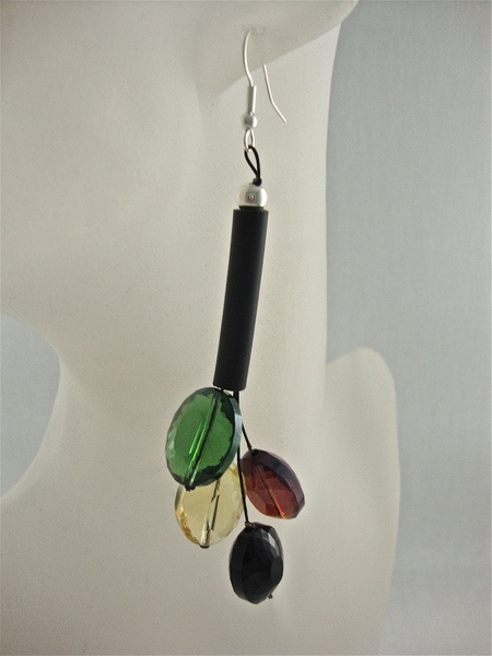 Ein Kautschuk Rohr an dem vier facettierte Glas Steine hängen. Eine glänzende Kombination in grün, gelb, braun und schwarz. Ohrringe fü r jedem Anlass