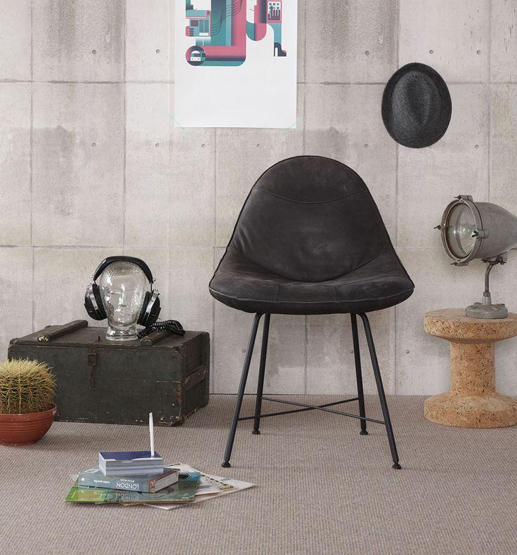 Behang met beton look van @eijffinger, stoer zwart leren stoeltje @labeldesign  en industriële accessoires. Desso Rodin