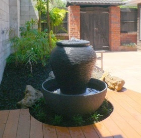 Where garden, deck and stone wall meet. Circular cut out and water feature. Designed by Fusion Landscape Design. Soft planting installation also by Fusion.