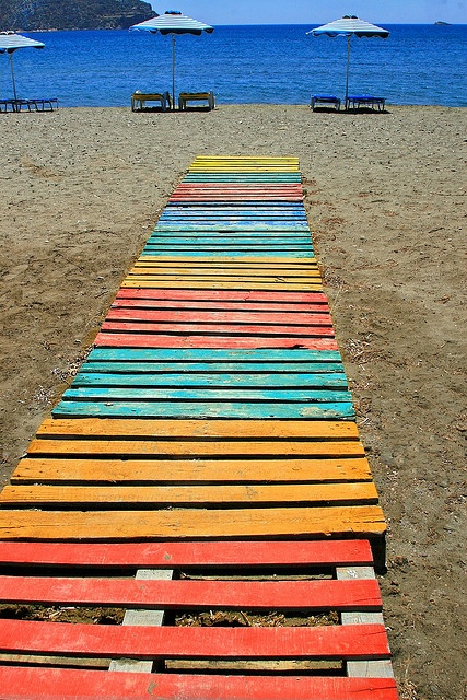 Multicolored wooden walkway and umbrellas at #Gournas #beach #Leros #island #Dodecanese #Greece