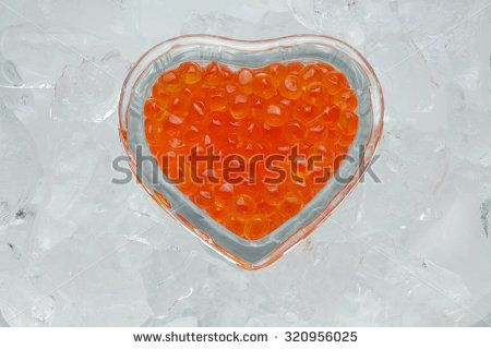 Red caviar in a heart shaped bowl on ice / ice heart / isolated on white background