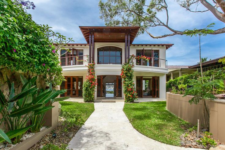 Classic Contemporary Spanish Style Beach House   contemporary Architecture   Spanish style mansion   tropical gardens   bougainvillea   grand entrance   timber windows   timber kitchen   waterfront   Sydney   boat house   open plan   modern house   indoor outdoor fireplace   glass ceiling    art deco   outdoor kitchen  
