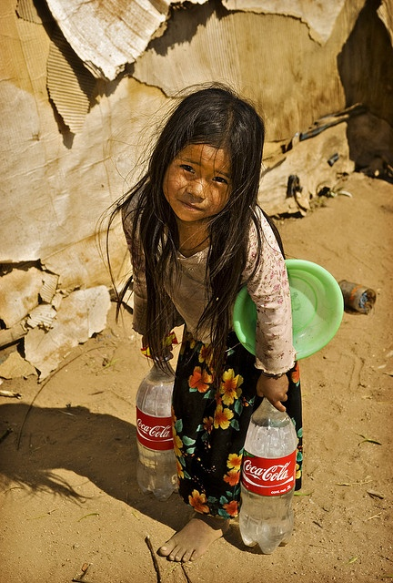Hauling water, collected from an irrigation ditch, up-hill to her family's shack. - Mexico