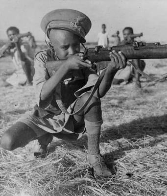 Enfant soldat éthiopien pose avec son fusil, coiffé dun bonnet italien pris à