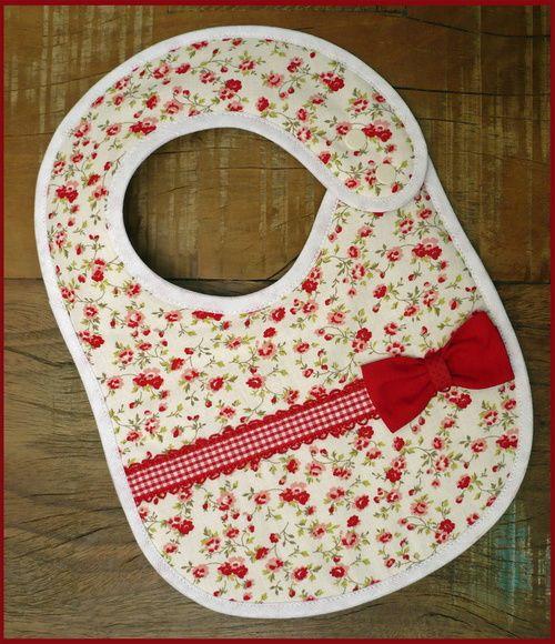 Babador vermelho em Patchwork com fitinha decorativa e laço. Tecidos 100% algodão, forrado com manta acrílica. Fechamento com botões de pressão, duas regulagens. R$ 17,50