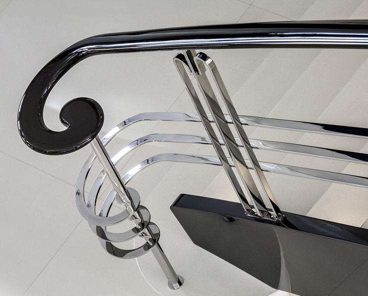 ST655 Schody na łukowej wylewce betonowej. Policzki i poręcze wykonane z dębu malowanego na czarno na wysoki połysk, wypełnienie balustrady ze stali szlachetnej szlifowanej na wysoki połysk. Realizacja w domu prywatnym, projekt – TRĄBCZYŃSKI