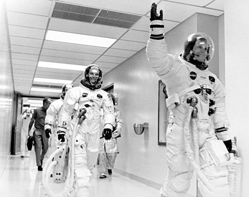 Apollo 11 Commander Neil A. Armstrong, waving, walks in a hallway of the Manned…