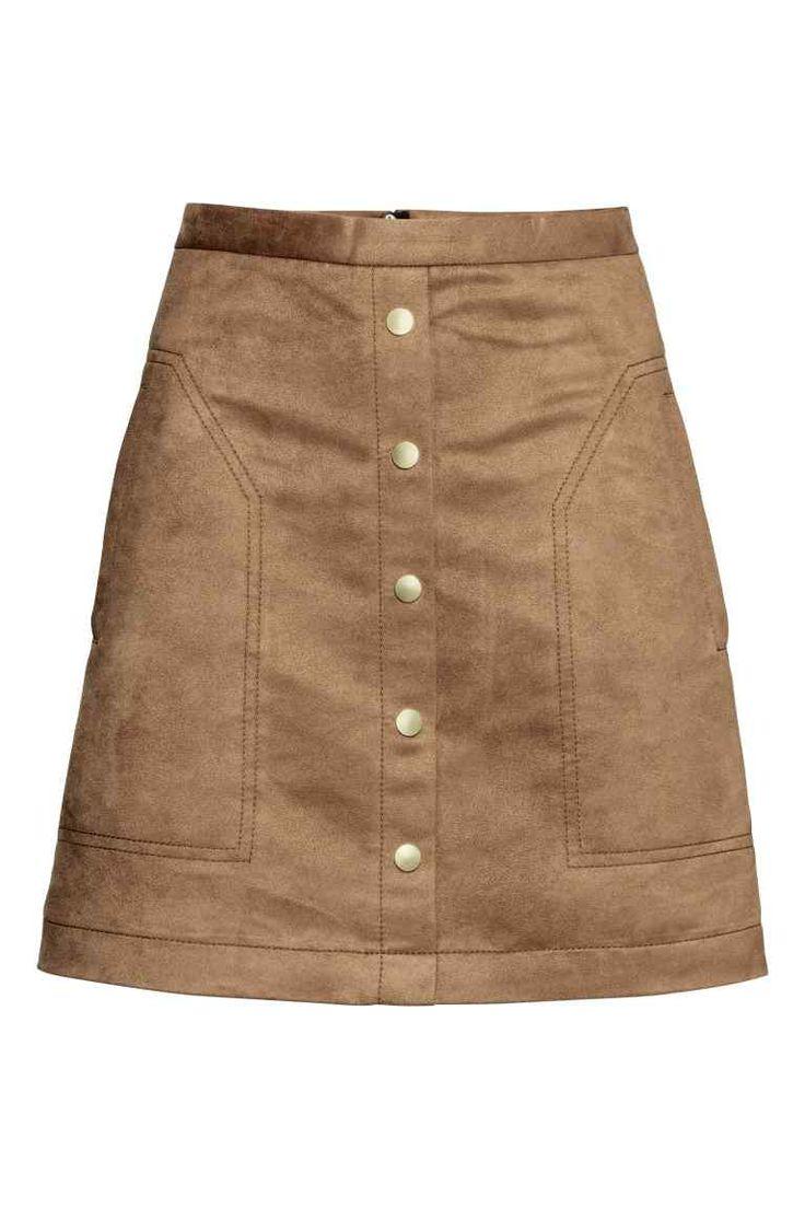 Jupe courte: Jupe courte avec boutonnage décoratif devant. Modèle avec fermeture à glissière dissimulée dans le dos.