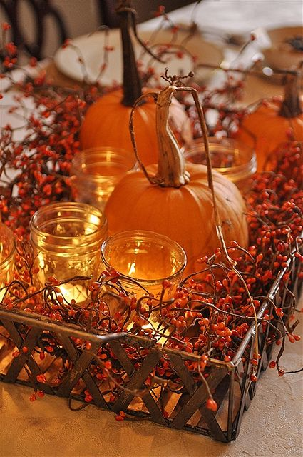 Centerpiece with pumpkins and candles gives an orange glow.