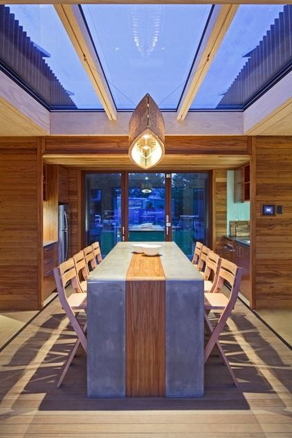 kitchen dining located in central breezeway skylights and doors leading to deck: triple glazed and argon filled with thermally broken timber frames to ensure best insulation but to feel connected to the outside at all times. Beach Style Dining Room by First Light Studio