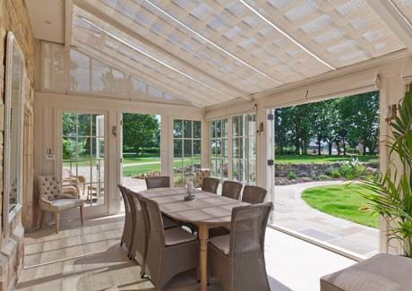 Dining in style with views out to the garden. Roof and side blinds were fitted to make the room more comfortable when entertaining.