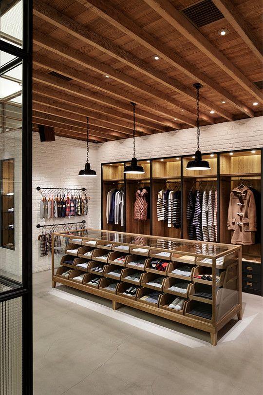 """Rustic Modern"" MACKINTOSH社のカジュアルブランドの旗艦店が、MACKINTOSH青山店と同じビルの地下にオープン。ハンドペイントで施された服のパターンなどが描かれた白い壁面のあるエントランスから階段を下りると、カジュアルなウェアーを受け止める空間があらわれる。店内は中央のグラスキューブを中心に様々な顔を持つエリアを作っている天井の無垢の木材に象徴されるナチュラルさ、ファクトリーのような空気を醸し出しながら英国らしさもあり、上階と深層ではつながっていることが見て取れる。"