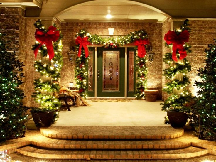festive porch and home entrance christmas decor featuring lighted green garland with red bow around the door and lighted garland wrapping porch column idea