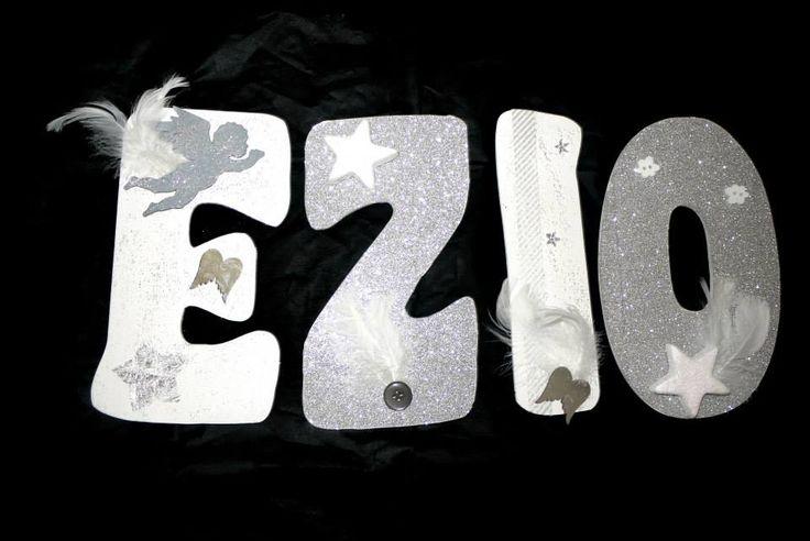 Ezio (ange + étoiles) j'ai décidé de peindre le E et le I en blanc et de coller un papier d'embellissement scrapbooking argenté, pailleté su le Z et le O.  Un ange peint en gris avec des plumes, un miroir « ailes d' ange » et une étoiles argentée sur le E. Une étoile blanche pailletée en relief, 2 plumes et un bouton gris sur le Z. Du masking tape gris et blanc, des ailes d anges miroir, des plumes et deux étoiles scintillantes sur le I. Une étoile avec des plumes et 2 boutons nuages sur le…