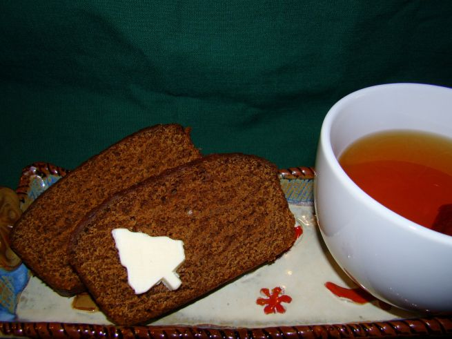 Dutch Breakfast Bread served with a pat of butter (shaped like a Christmas Tree for the holidays) and a cup of hot tea.
