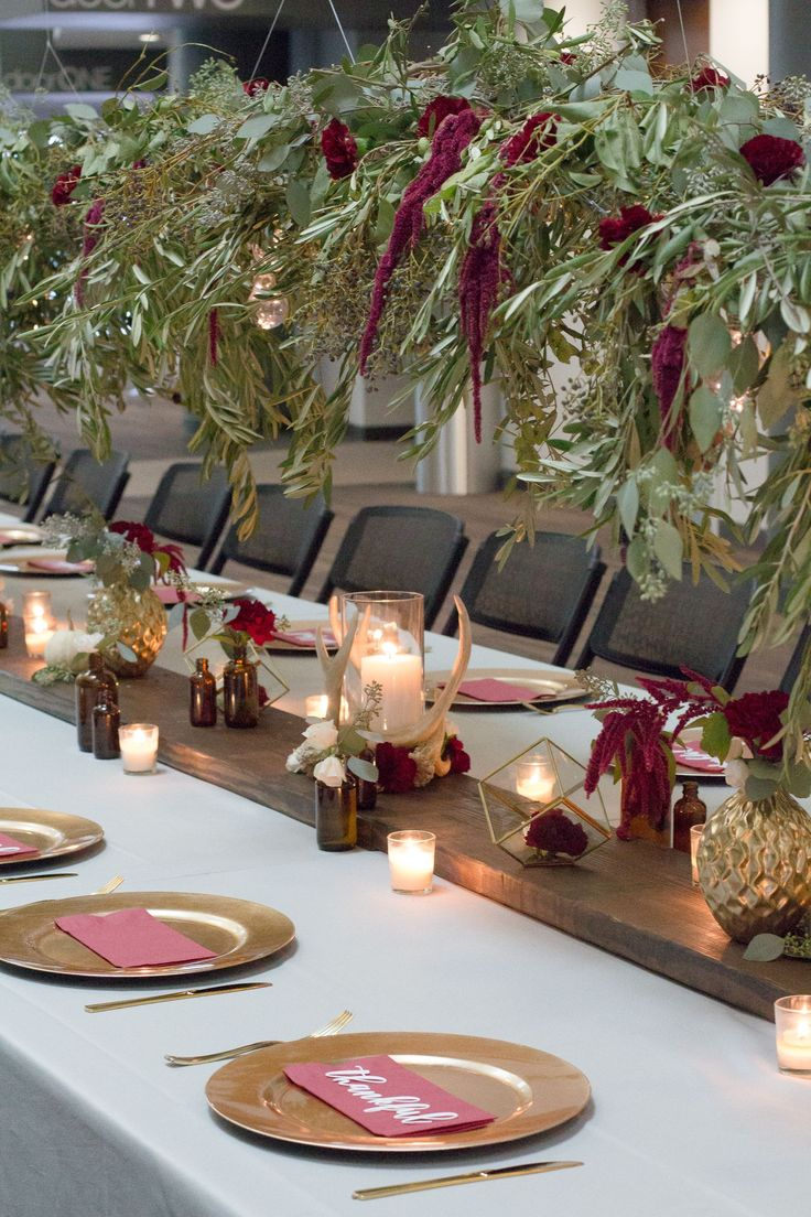 Tons of tips from Sweetwood Creative Co. on how to create a lush, gorgeous fall or Thanksgiving tablescape on a budget like this gorgeous burgundy, gold and gray table with greenery and wood accents and a floral chandelier!  Thanksgiving decor | thanksgiving inspiration | event decor | event planning | wedding centerpieces | burgundy and gold centerpiece | olive branches | eucalyptus | seeded eucalyptus | bistro lights