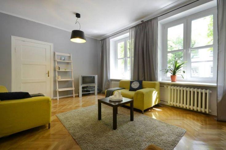 Bardzo duży i wysoki salon urządzono w prostym skandynawskim stylu. Wnętrze zdecydowanie dekorują żółte fotele, poza tym dekoracje są zastosowane w oszczędnej formie. Biały regalik pod ścianą w formie drabiny podkreśla klimat pokoju dziennego.