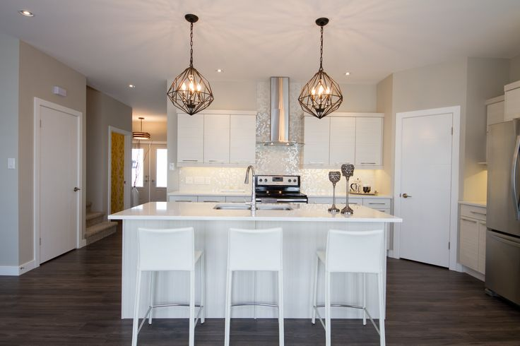 Neutral Galley shaped Showhome Kitchen with Pendant lighting and stainless steel fixtures