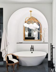 A Ralph Lauren Home light fixture illuminates the master bath's Victoria + Albert tub in Naomi Watts and Liev Schreiber's Ashe + Leandro–designed New York City apartment, which has Dornbracht fittings; the mirror and chair are antique, and the penny tile is by Waterworks.