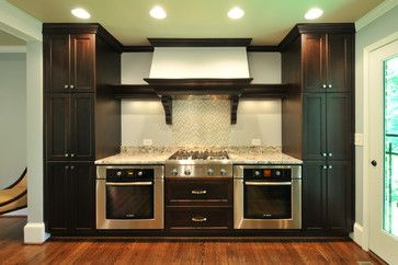 Base single ovens, alone or in tandem. Another arrangement is a separate wall oven or two in base cabinets. Shown here flanking a range top is a pretty unusual setup. Some might ask why not just do a 60-inch range with two full-size ovens and more burners? Sure, that would work, but in this case the homeowner is getting a bit more counter space.