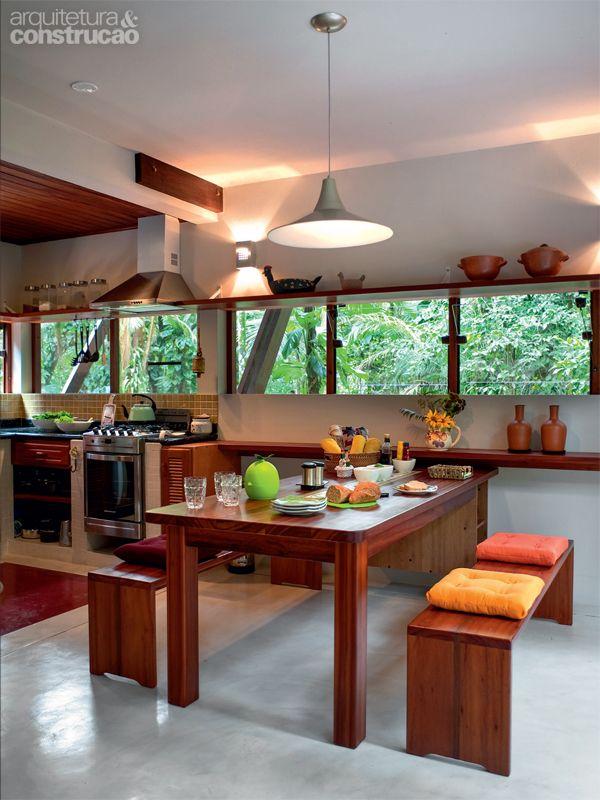 De volta ao térreo, na cozinha, janelas basculantes trazem luz e deixam a brisa circular. Projeto de André Guidotti.