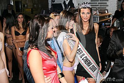 Two models in a famous Italian beauty contest. Two beautiful girls are participating in a famous contest of feminine beauty in Italy in Rome. December 12, 2009. Rome, Italy. White club. The winner, with a crown on the head, and one of the participants smiling in front of the photographer.