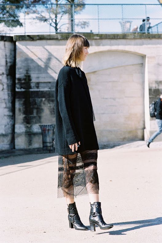 A black sweater is perfectly layered with a lace slip dress and finished off with black boots