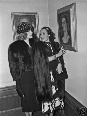 Dolores Del Rio and Marlene Dietrich admire a Frida Kahlo self portrait, 1930s