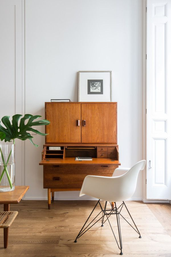 small workspace with mid century modern secretary and white molded plastic eames chair
