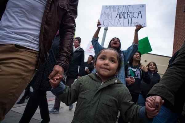 In this Feb. 27, 2017 staff file photo, Luna Morales, 5, holds onto her parents Fernando Herrera and Margarita Villanueva as they march from the Pasadena Job Center to City Hall to ask the Pasadena City Council to make Pasadena a sanctuary city.