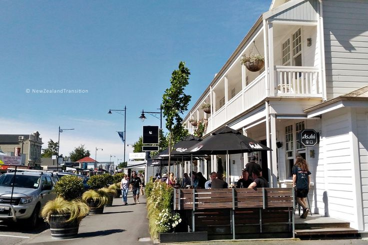 tourists sitting in sunshine outside the White Swan bar, Greytown