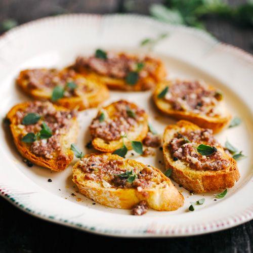 Doe de olie, knoflook en ansjovis in een blender en hak grof. Smelt de boter in een pan, voeg het ansjovismengsel toe en verhit een paar minuten. Rooster het brood goudbruin. Besmeer het dun met de bagna cauda en bestrooi met oregano.
