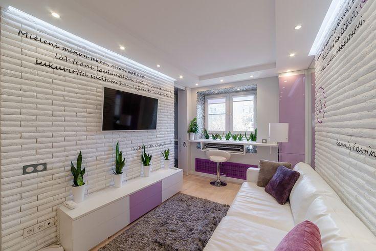Белый диван с разноцветными подушками в гостиной и мягкий серый пол делают квартиру очень уютной. Комнатные растения создают в помещении цветовой акцент