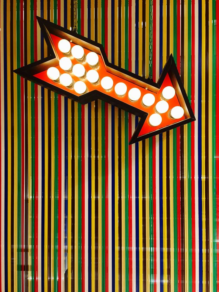 A lit-up luminous orange arrow pointing on the lower right over a multicolored plastic background. Arrow Background Backgrounds Bright, Colored Colours Decoration Design Illuminated Indoors  Interior Light Light And Shadow Light Bulb Lit Lit Up Luminosity Luminous Multicoloured Orange Plastic Pointing Striped Stripes Pattern White