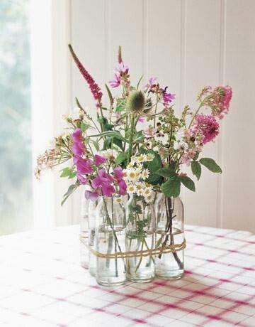 Bello arreglo floral con botellas de vidrio. Excelente para una casa campestre.Flor Fossatti.