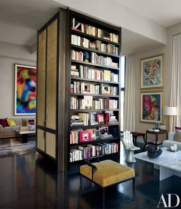 Drake added the living room's floor-to-ceiling cabinet, with storage and bookshelves, to conceal a structural column; the photographs on the wall at right are by Alexandra Penney | http://archdigest.com