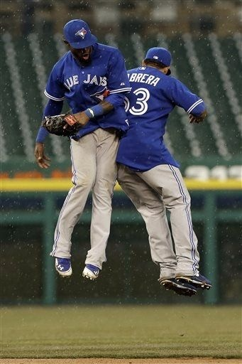 Toronto Blue Jays Jose Reyes, left, and Melky Cabrera celebrate after defeating the Detroit Tigers 8-6 in a baseball game in Detroit, Wednesday April 10, 2013. (AP Photo/Paul Sancya)