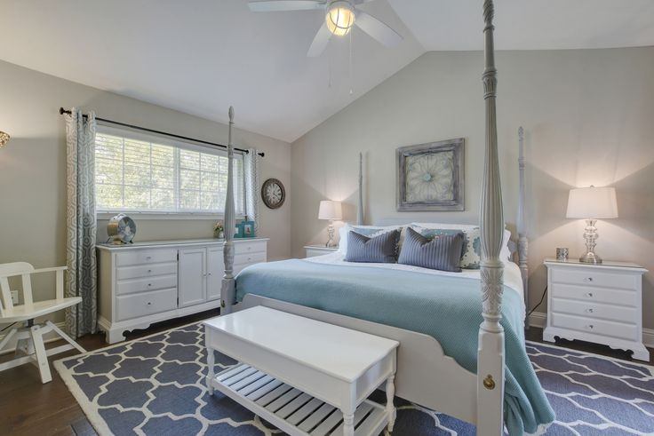 Benjamin Moore Revere Pewter paint in master bedroom with grey 4 poster bed, geometric rug and white furniture.
