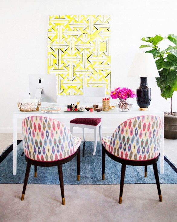 Eva Chen's office at Lucky Magazine with bright art and printed chairs.