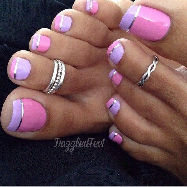 An adorable looking inverted French tip for the toes. A pleasing toenail art design using pink, periwinkle and silver colors. The nails are painted with inversing colors for each tip with a thin line of silver for the edges.