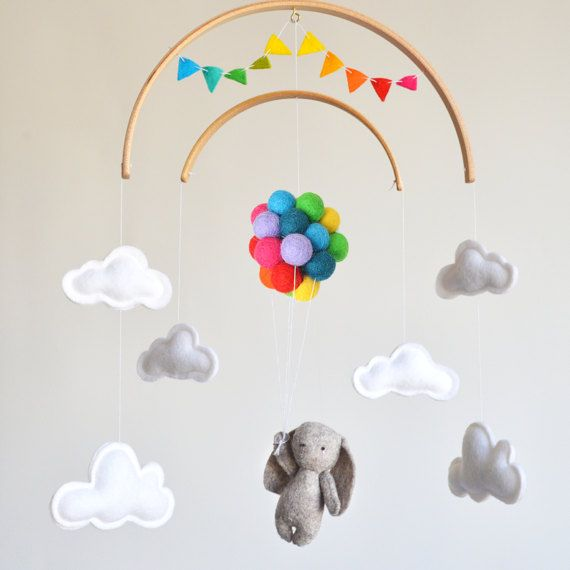 Neutral baby mobile featuring a little bunny flying balloons, surrounded by clouds with a rainbow bunting banner Hi! and thank you for visiting my shop! ❤ This adorable neutral gender baby mobile will capture everyones attention and would make the cutest addition to any nursery decor. ❤ The little bunny is hand stitched by me. All items are handmade with 100% wool felt, bunny and clouds are filled with hypo-allergenic polyester stuffing. The 27 multicolor balloons are sewn together and…
