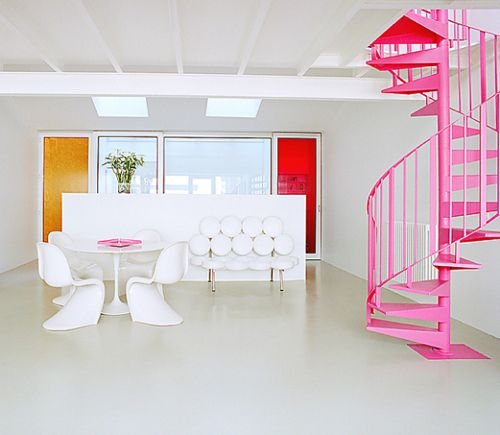 12 White Rooms with Pops of Color: In this image by French interiors photographer, Bruno Suet, mid-century furniture is set off in a minimalist setting that could be the model for a contemporary dollhouse for Barbie, given the bubblegum pink spiral staircase.